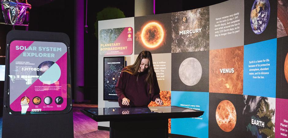 Patron using touch screen exhibit.